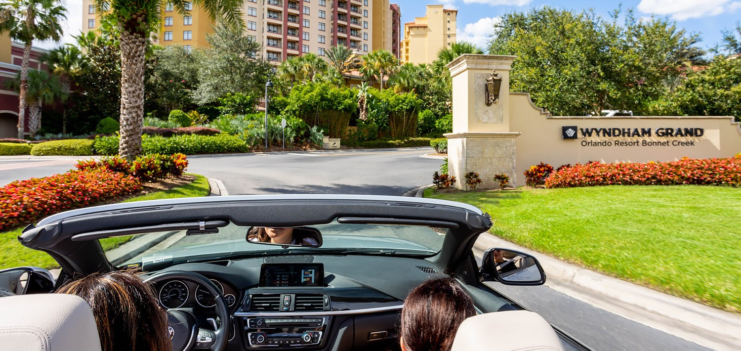 women driving a convertible car up to the entrance of the hotel