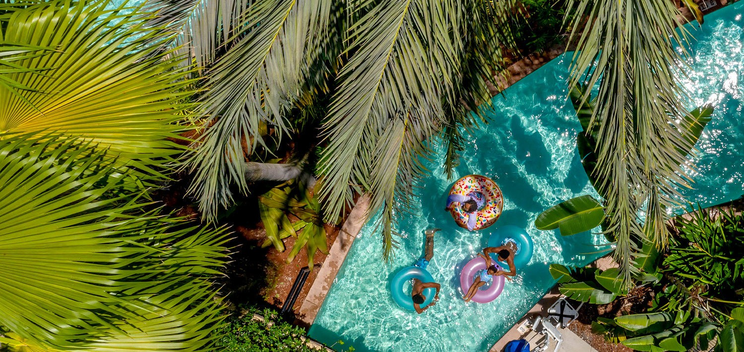 a family going down the lazy river pool in inner tubes