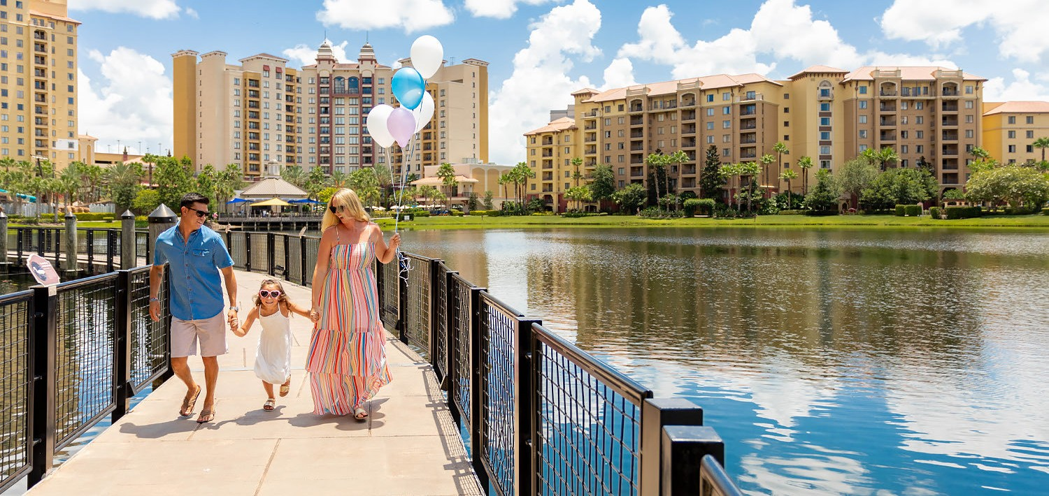 a family walking down a boardwalk with balloons on a sunny day