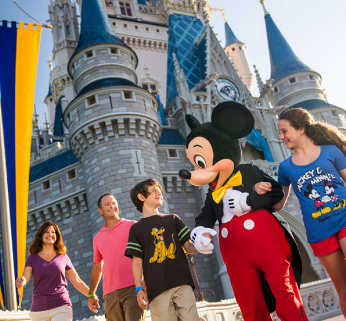 mickey mouse and family walking together in front of Cinderella's Castle at Magic Kingdom