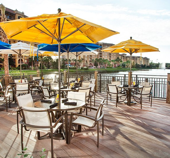 deck patio with tables and chairs under yellow umbrellas