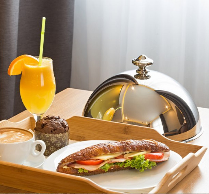 wooden room service tray with sandwich coffee and juice