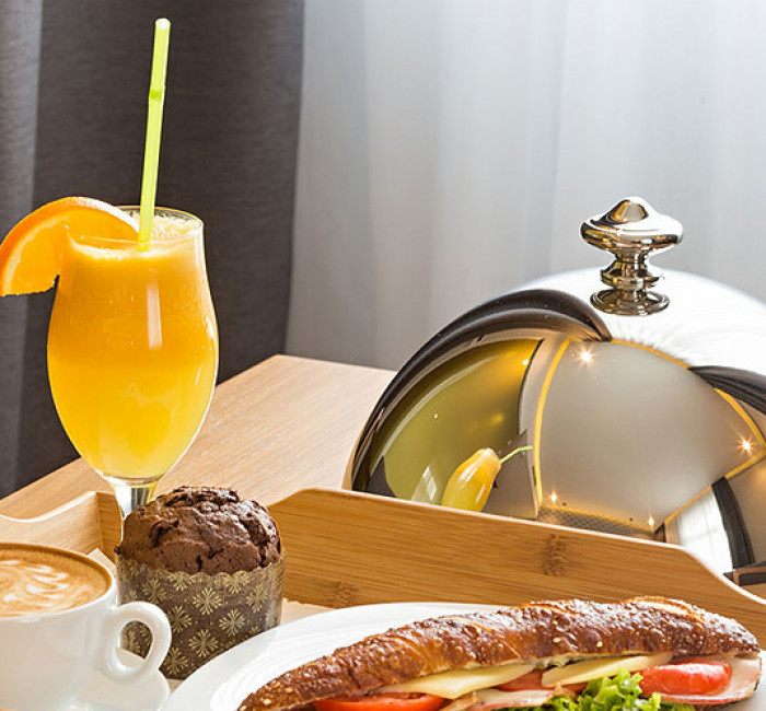 wood room service tray with toasted sandwich muffin coffee and orange juice