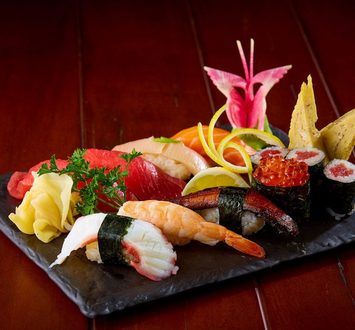 black plate with arrangement of sushi and flower dressings