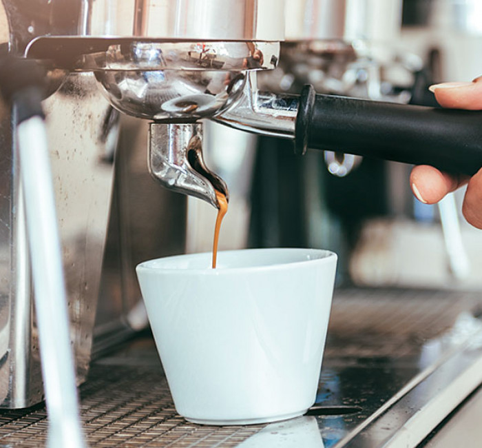 white espresso cup being filled up by a stainless espresso machine