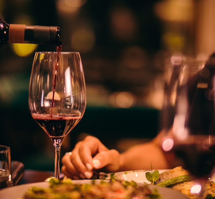 woman enjoying dinner with a glass of red wine