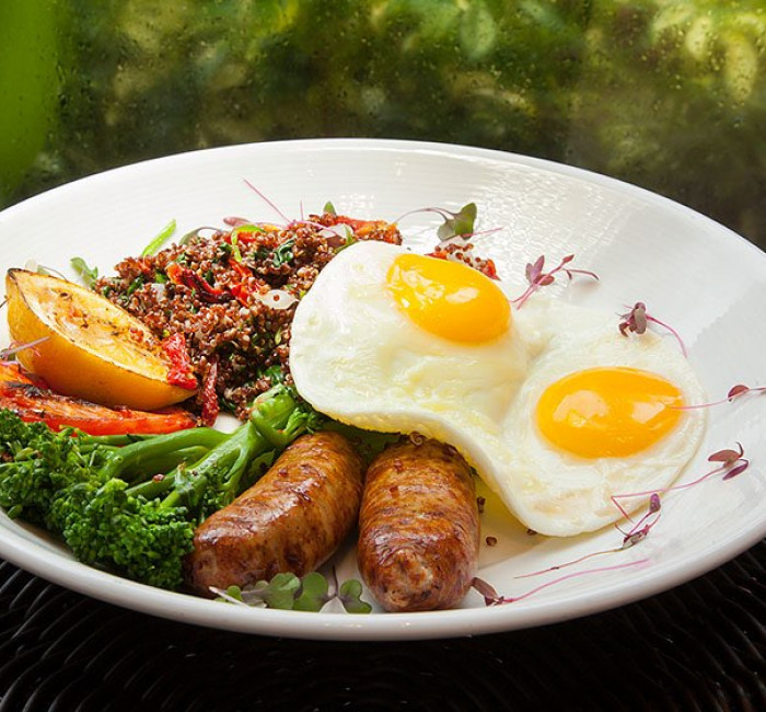 sunny side up eggs sausage and greens on a white round plate