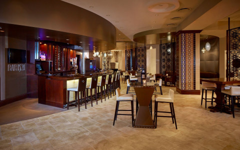 hotel bar area with curved wooden bar top and high-back white stools