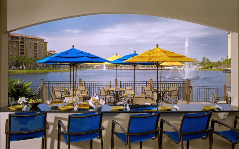 deck area with tables and chairs under yellow and blue umbrellas and lake with fountain in background