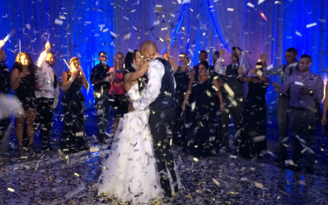 newlywed couple dancing on a dance floor with confetti raining on them