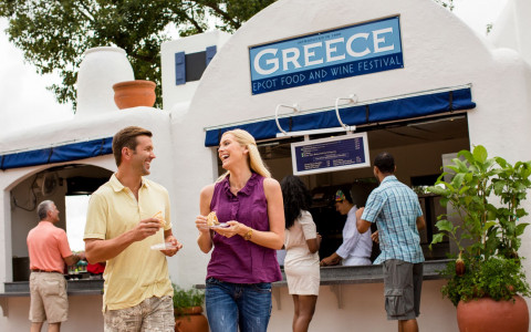 Couple enjoying Greek food at Epcot's Food & Wine Festival