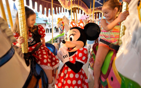 Minnie Mouse riding a carousel with two children