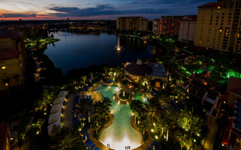 arial view at night of hotel and surrounding property with lake in background