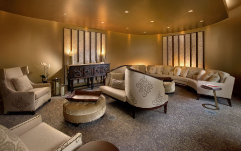 spa waiting area with gold ceiling and beige curved couch and chairs