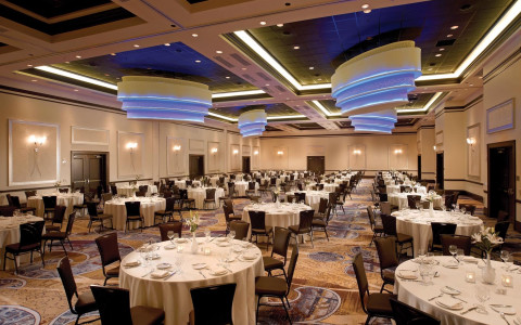 large event space with recessed ceilings and round tables arranged in rows