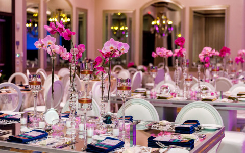 event space dining table with white chairs and pink floral arrangements