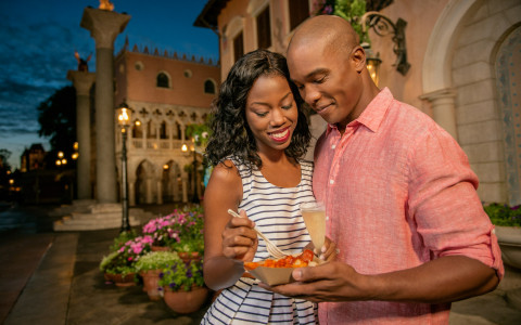 couple sharing food together and smiling at Epcot Center World Showcase