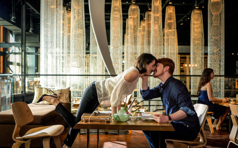 woman leaning over dining table to kiss man