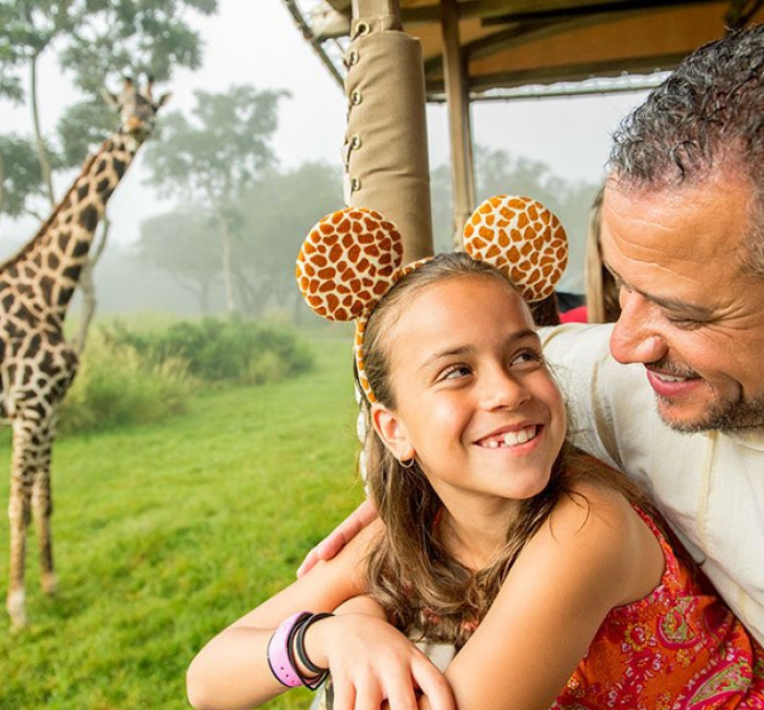 Happy father and daughter on a safari ride at Animal Kingdom passing by a Giraffe