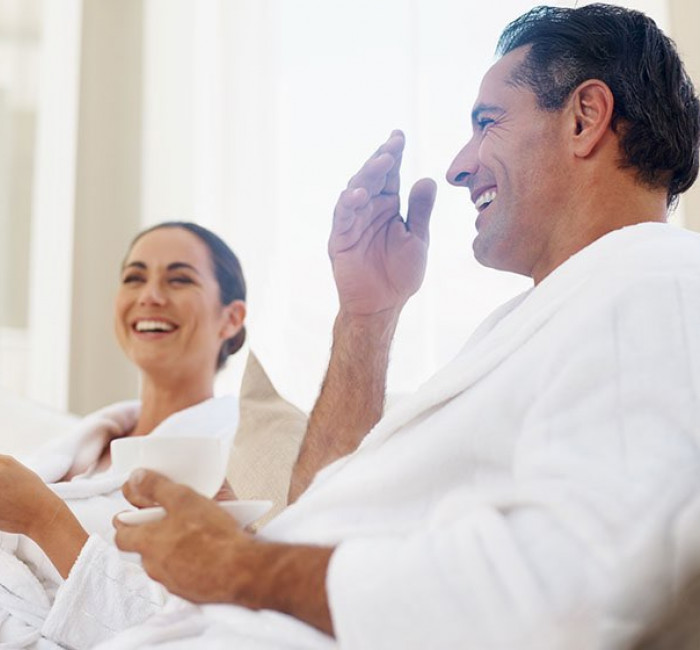man and woman laughing together wearing white spa robes