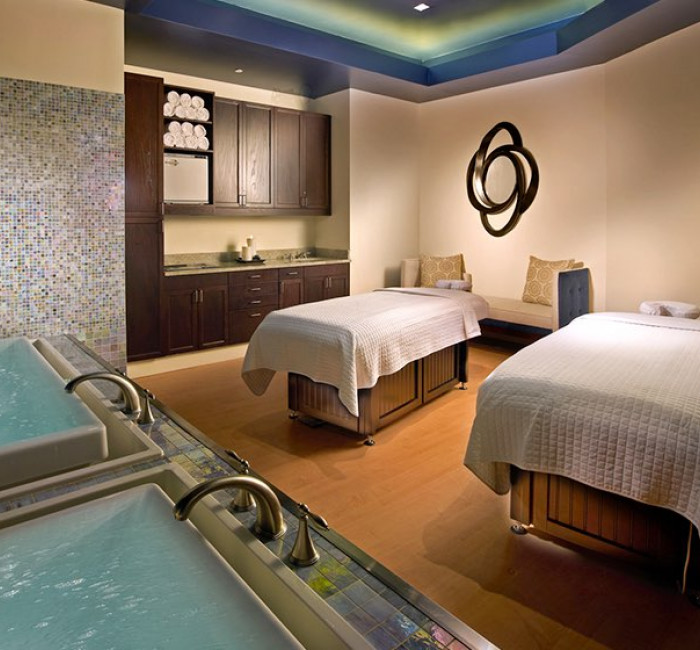 massage room in spa with two massage tables and white towels