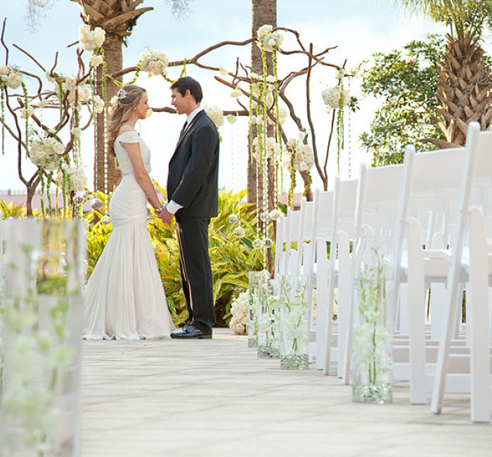 wedding couple standing at altar at the end of an aisle with white chairs in rowed seating