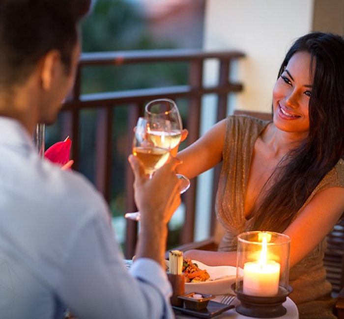 woman and man smiling and toasting wine glasses by candle light