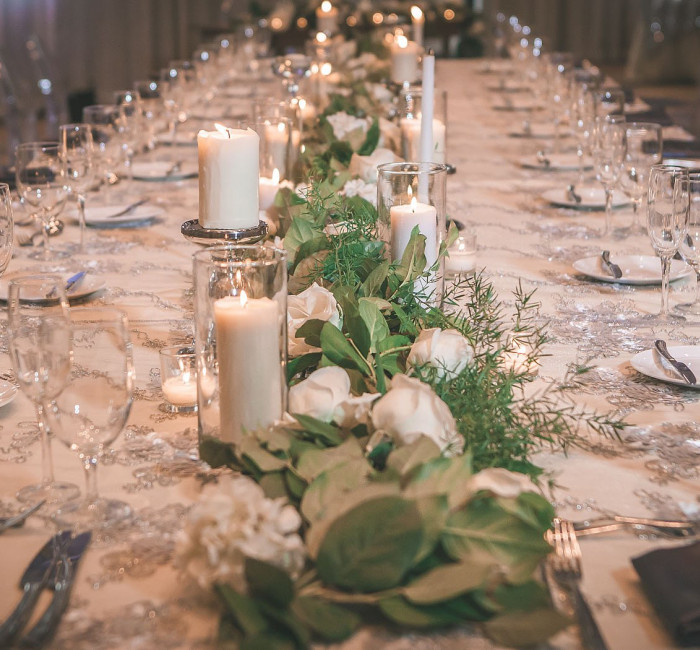 long table with white table cloth and flowers arranged with place settings