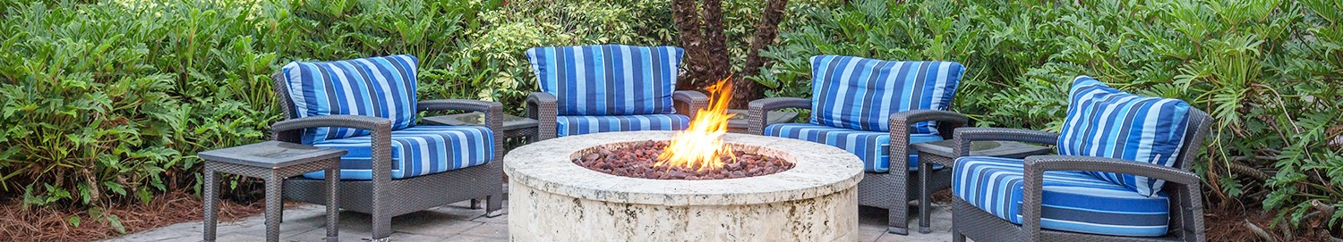 comfy sofa chairs surrounding a fire pit