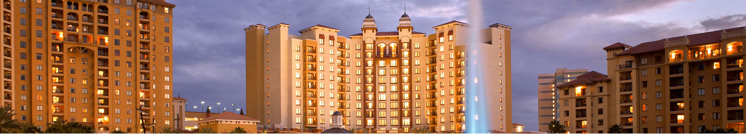wide image of the hotel at night with lighted windows