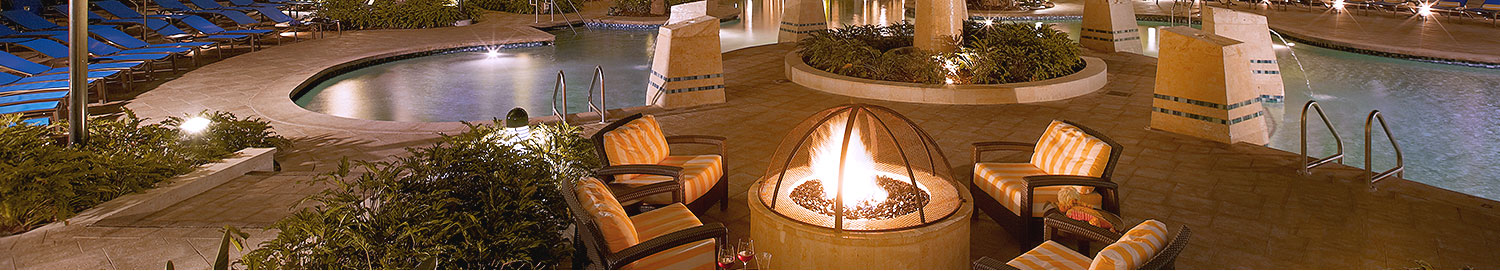 Pool area at night with glowing fire pit surrounded by lounge chairs