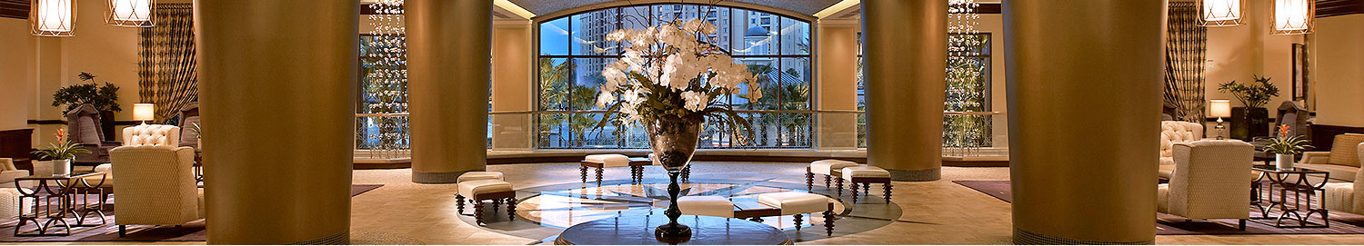 lobby sitting area with large curved window in background and table with white flowers in foreground