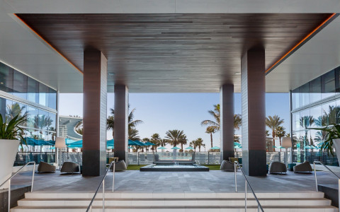 Hotel entrance with view of pool and palm trees
