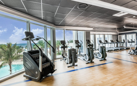 Fitness center with equipment overlooking pool through large window panels