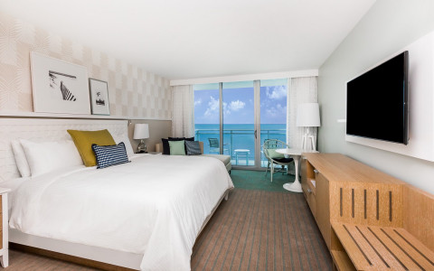 Roomw ith king bed, tv * seating area by balcony with beach view