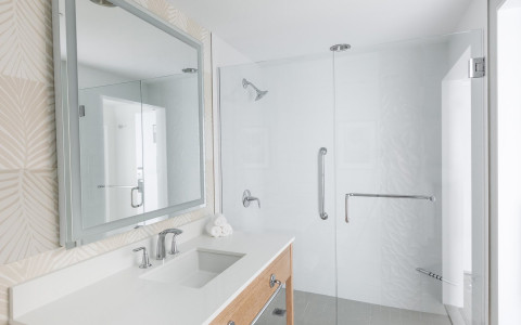White bathroom with vanity, sink & glass door shower