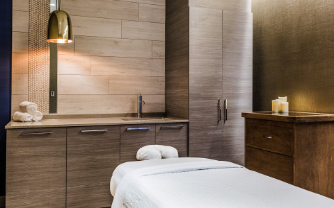 Close up of spa bed in room with warm wooden cabinets