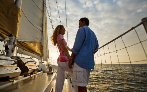 Couple standing on sailboat on the water