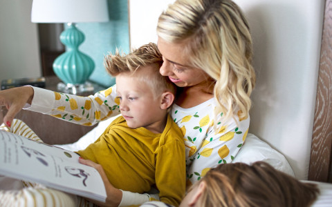 Woman reading book to little boy in bed