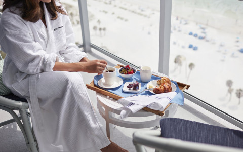 Close up of woman in robe enjoying breakfast by the window view