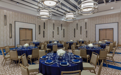 Meeting space with tables set with blue tablecloths