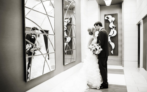Black and white image of wedding couple kissing indoors