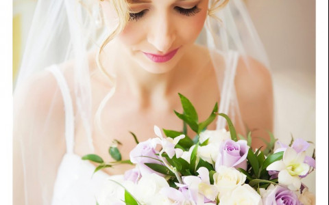 Close up of woman holding bouquet of white and lilac roses