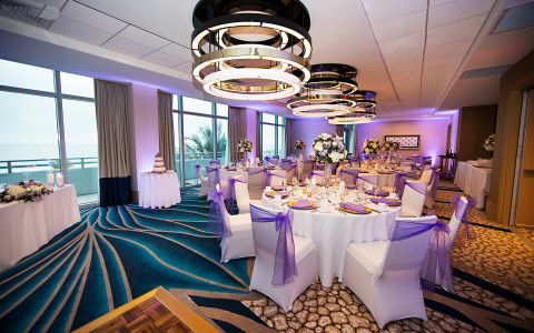 Room set for wedding reception with lilac accents