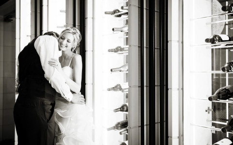 Black and white image of groom kissing bride on cheek
