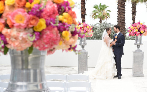Wedding couple standing in courtyard with roses bouquets