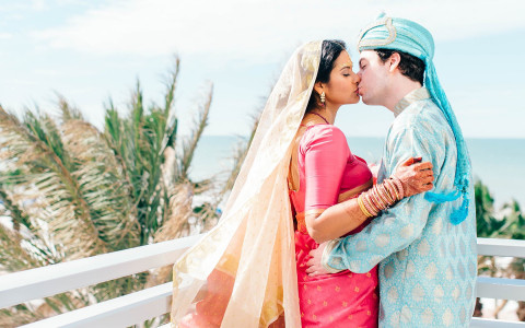 Kissing wedding couple dressed in authentic indian wedding garments