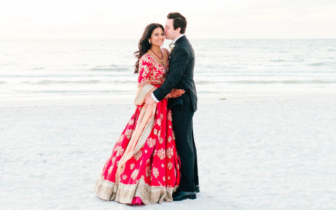 Wedding couple standing by ocean shore