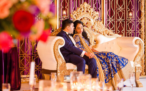 Wedding couple dressed in indian garments sitting on couch