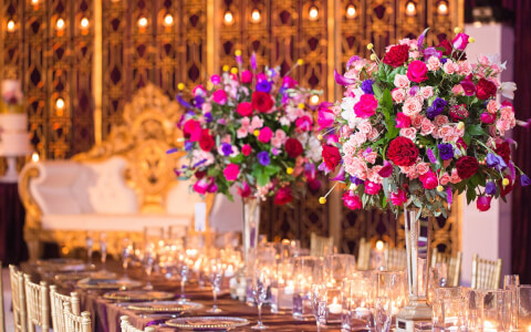 Long table set up for wedding reception with multiple shades of pink flowers